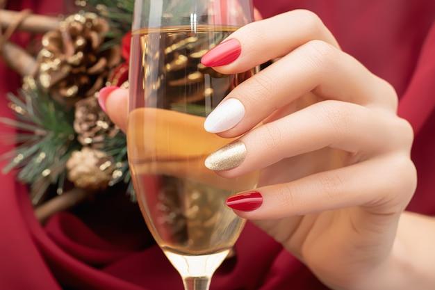 Mano femminile con unghie rosse design tenendo un bicchiere di champagne a natale.