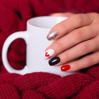 Mano femminile con unghie manicure romantica, disegno del cuore