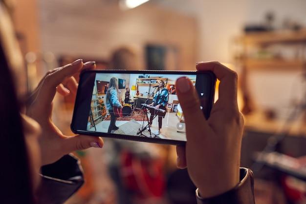 Mano femminile con smartphone durante le riprese video di performance musicali