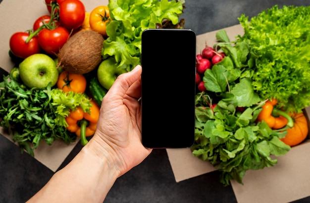 Mano femminile con smartphone e scatole piene di diverse verdure fresche biologiche