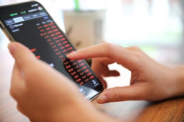 Mano femminile con smartphone trading stock online nella caffetteria