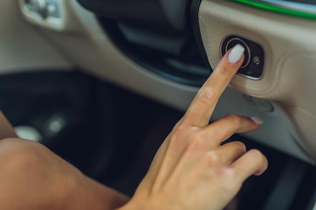 Mano femminile con chiave di avviamento all'interno dell'auto