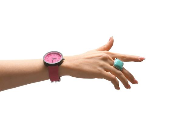 Mano femminile con elegante orologio e anello sulla superficie bianca