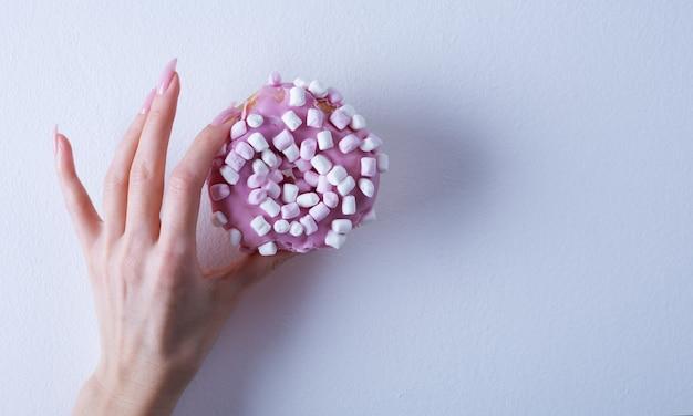 Mano femminile con manicure in marmo alla moda che tiene la ciambella. nail design rosa primavera estate.