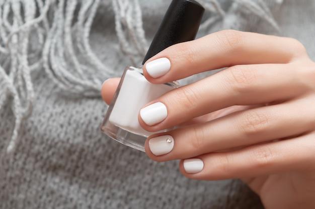 Mano femminile con il disegno bianco dell'unghia che tiene la bottiglia dello smalto.