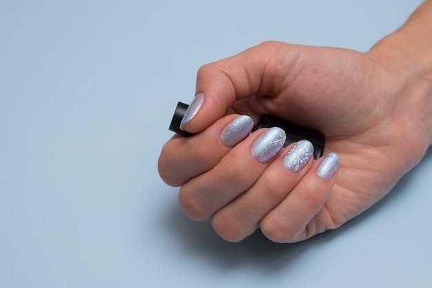 Mano femminile con manicure invernale e una bottiglia di smalto per unghie