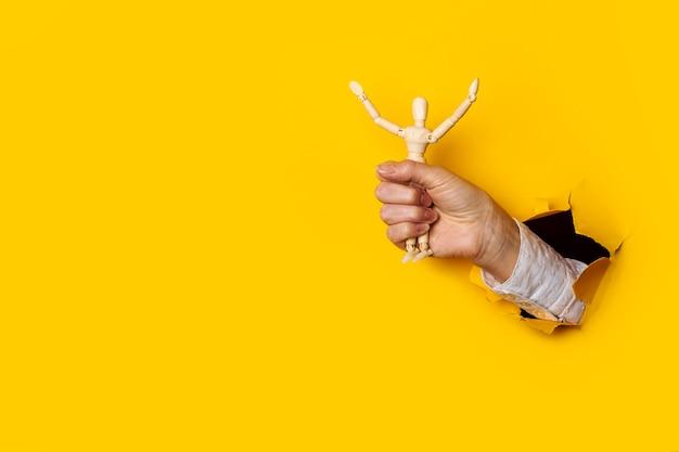 Mano femminile con un burattino di legno dell'uomo in un buco strappato