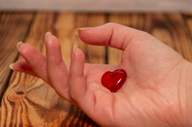 Una mano femminile su uno sfondo di legno tiene un cuore.