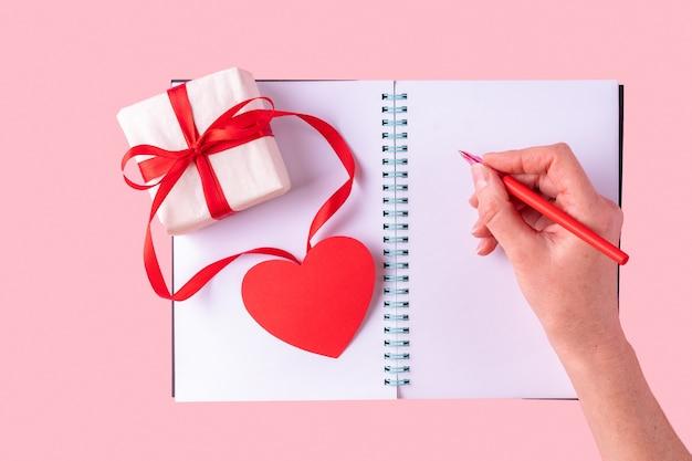 La mano femminile scrive un messaggio di amore con una penna rossa in un taccuino aperto in bianco bianco