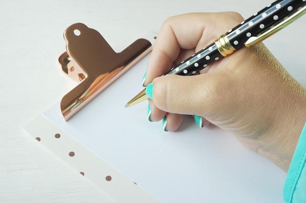 La mano femminile scrive con una penna a sfera su un foglio di carta pulito su una lavagna per appunti.