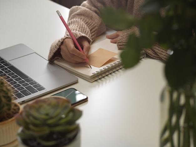 Scrittura femminile della mano sul taccuino in bianco