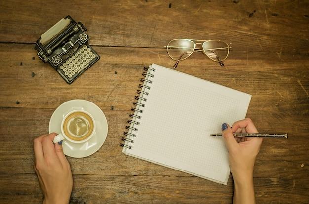 Mano femminile che scrive in taccuino sul tavolo