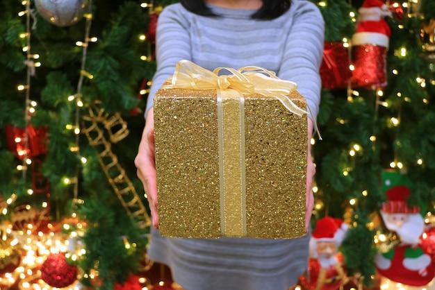Donna che consegna una confezione regalo glitter oro a qualcuno sfocato albero di natale