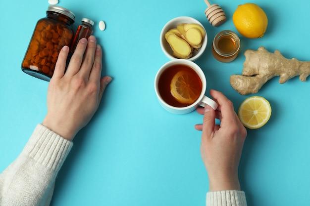 Mani femminili e medicine alternative sulla superficie blu, vista dall'alto