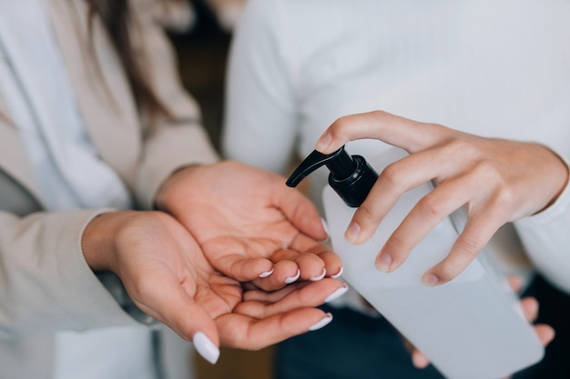 Mani femminili che applicano sapone liquido antibatterico