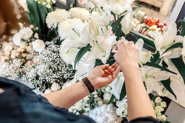Le mani femminili si prendono cura del giglio bianco del fiore. giardinaggio e concetto di piccola impresa. vista dall'alto
