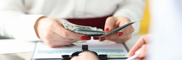 Le mani femminili stanno contando i contanti all'aumento del profitto del tavolo di lavoro nel concetto di affari