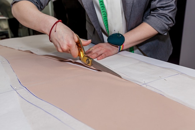 Le mani femminili stanno tagliando il tessuto con le forbici da sarti sul modello di carta, su un tavolo bianco