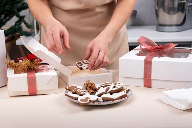 Le mani femminili stanno avvolgendo i biscotti di pan di zenzero in confezione regalo. scatola di natale. avvicinamento.