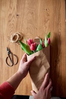 Mani femminili che sistemano il mazzo di tulipani rosa sul tavolo di legno, posto di lavoro di hobby floristico, affari, fai da te, concetto di regalo di primavera, dall'alto.