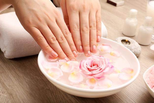 Mani femminili e ciotola di acqua termale con fiori, primo piano