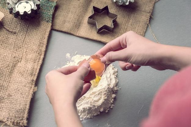 Le mani femminili rompono un uovo di gallina nella farina