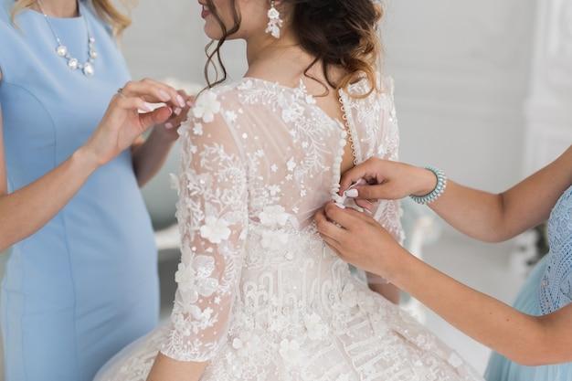 Mani femminili abbottonano l'abito da sposa alla sposa con una bella acconciatura