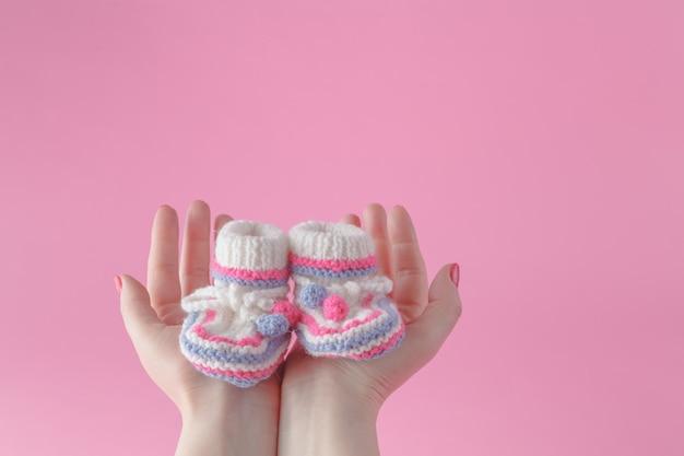 Mani femminili forando accuratamente le scarpe da bambino