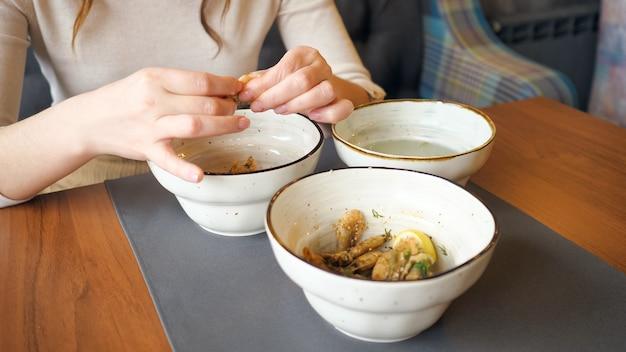 Le mani femminili puliscono e mangiano i gamberetti in caffè, primo piano
