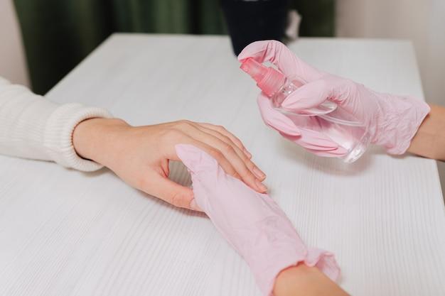Mani femminili si chiudono. le mani in guanti di gomma rosa trattano la pelle delle mani con un antisettico.