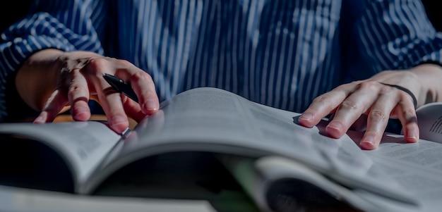 Le mani femminili si chiudono tenendo la penna e leggono molti libri concetto di banner orizzontale di istruzione