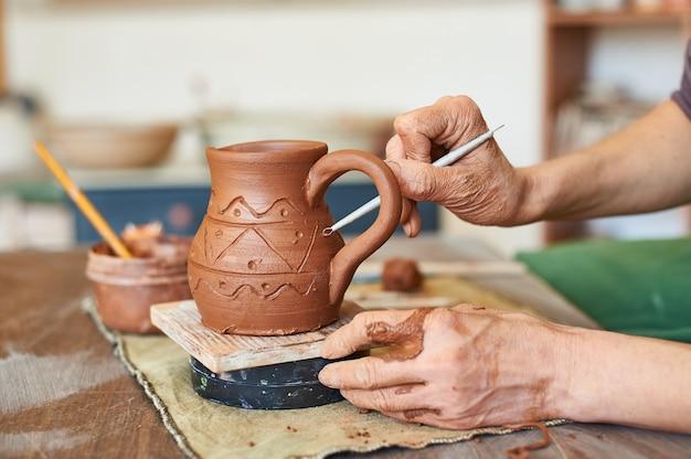 Le mani femminili si chiudono, il vasaio applica un motivo con uno strumento sulla superficie di una brocca di terracotta.