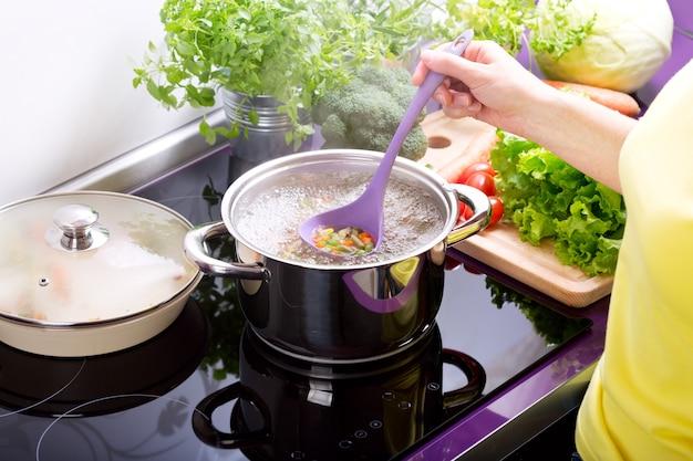Mani femminili che cucinano la minestra di verdura in cucina
