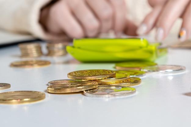 Mani femminili che contano i dati sulle tasse iva costano facendo scartoffie a casa ufficio tavolo, primo piano