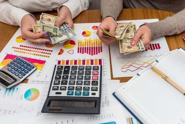 Mani femminili che contano dollari con grafici commerciali