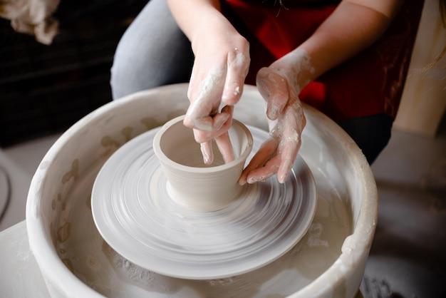 Mani femminili che creano una tazza di ceramica sul tornio di un vasaio.