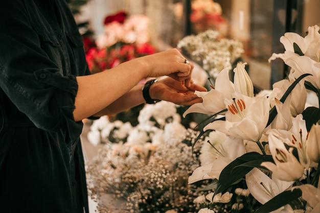 Mani femminili che creano bouquet di giglio bianco. lavoro di fiorista. hobby o concetto di piccola impresa
