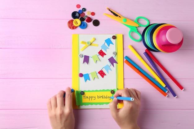 Mani femminili che creano una carta regalo su un tavolo di legno rosa