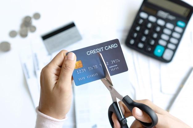 Mani femminili che tagliano la carta di credito con una forbice