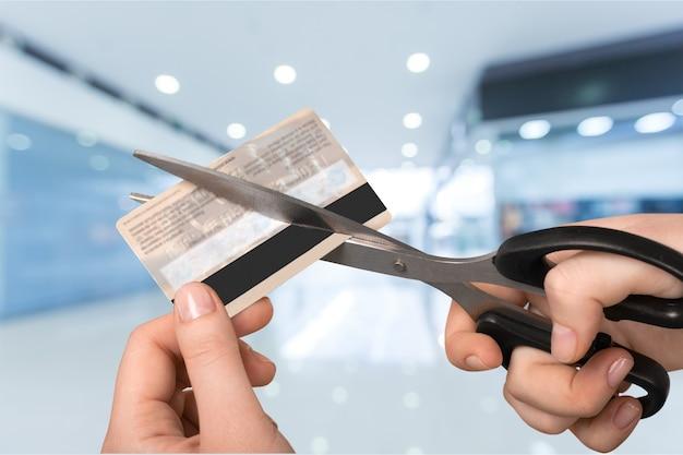 Mani femminili che tagliano la carta di credito con le forbici