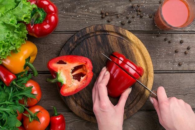 Mani femminili che tagliano pepe a tavola, vista dall'alto. sul tavolo foglie di lattuga, pepe, un bicchiere di succo di pomodoro, una tavola di legno e un coltello