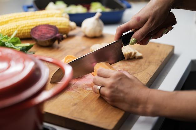 Mani femminili che tagliano la patata dolce su una tavola di cucina in legno piena di varie verdure autunnali.