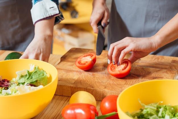 Mani femminili che tagliano le verdure per insalata in cucina