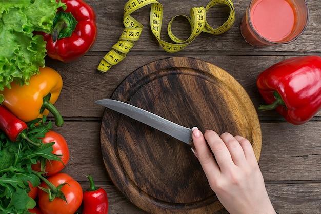 Mani femminili che tagliano le verdure alla vista del piano d'appoggio