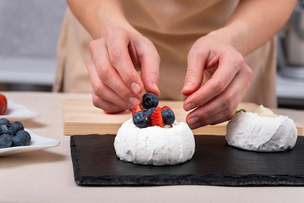 Mani femminili che decorano la meringa con mirtilli e fragole. processo di produzione di torte.