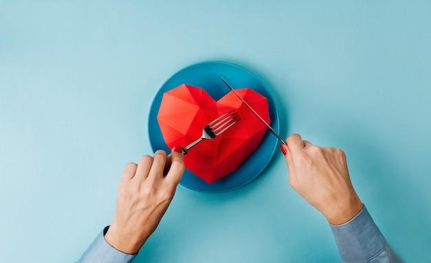 Mani femminili che mangiano il cuore del volume di carta sul piatto su superficie blu