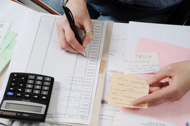 Le mani femminili compilano un rapporto contabile
