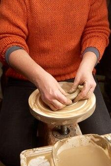 Mani femminili che formano pentola di creta sul tornio