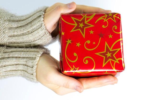 Mani femminili che danno un regalo di natale isolato su priorità bassa bianca