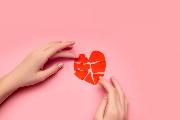 Mani femminili che incollano insieme cuore spezzato, pezzi di san valentino rosso strappato sul rosa